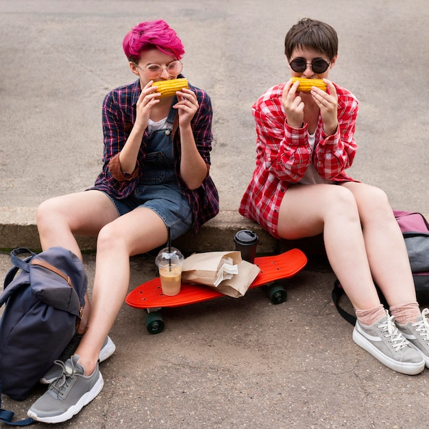 一緒にトウモロコシを食べるフルショットの女の子 無料写真