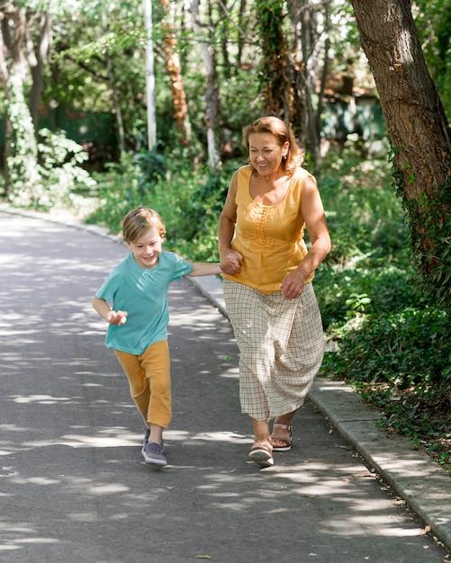 Full shot grandma and kid running Free Photo