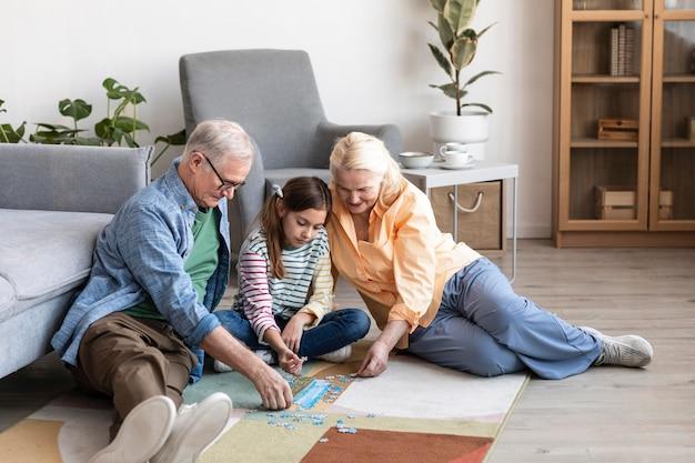 풀 샷 조부모와 퍼즐을하는 아이 무료 사진