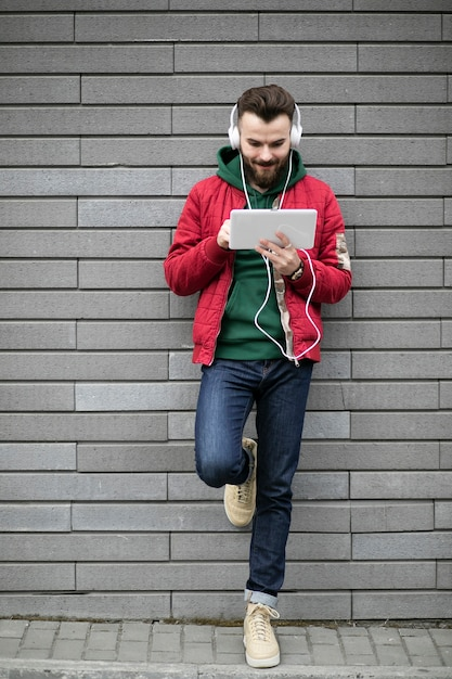 Full shot guy with headphones and tablet Free Photo