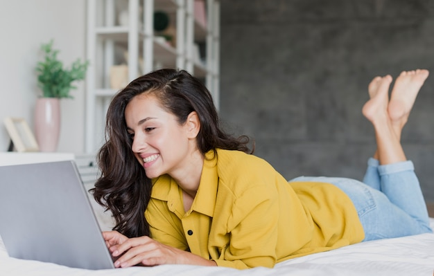 Full shot happy brunette woman with laptop Free Photo