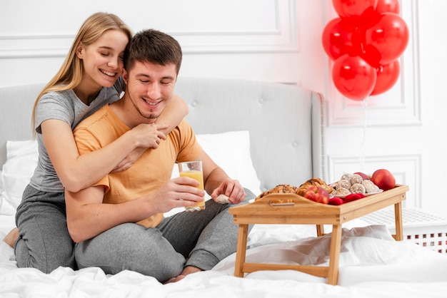 Full shot happy couple with breakfast in bed Free Photo