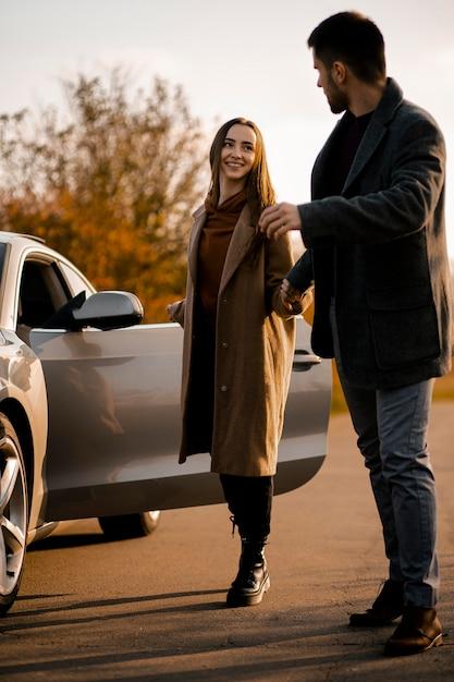 Полный снимок счастливая пара с автомобилем Бесплатные Фотографии