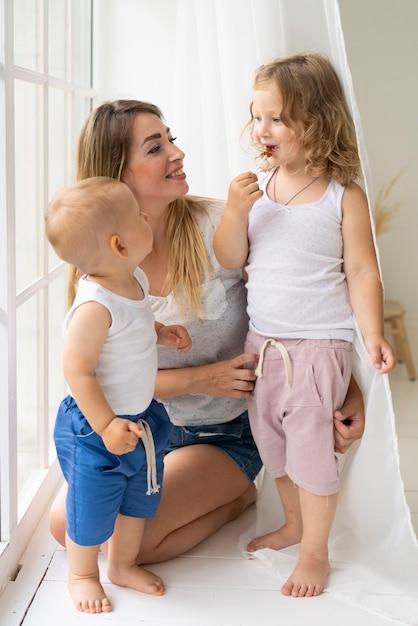 彼女の子供と一緒にいるフルショット幸せな母 無料写真