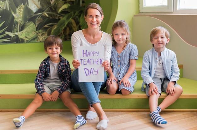 Полный снимок счастливый учитель позирует с детьми Бесплатные Фотографии