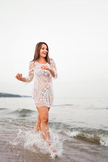海でポーズをとってフルショット幸せな女 無料写真