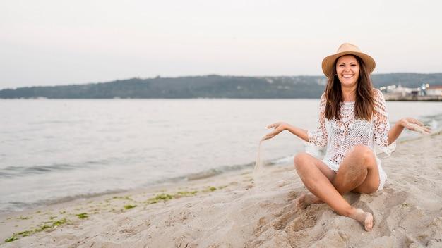 Полный снимок счастливая женщина, сидящая на берегу Бесплатные Фотографии