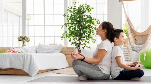 一緒に瞑想するフルショットの子供と大人 Premium写真