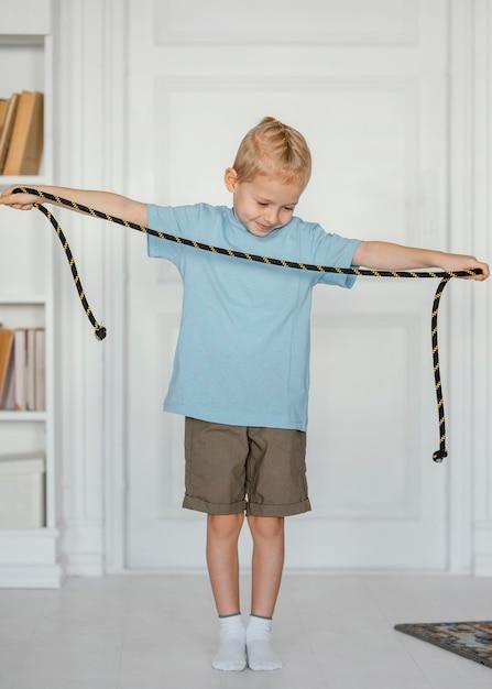 점프 밧줄을 잡고 전체 샷된 아이 무료 사진