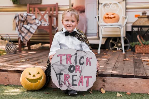 Полный ребенок держит знак трюк или угощение Бесплатные Фотографии