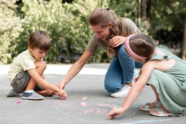 Полный кадр дети и учитель рисуют на земле Бесплатные Фотографии