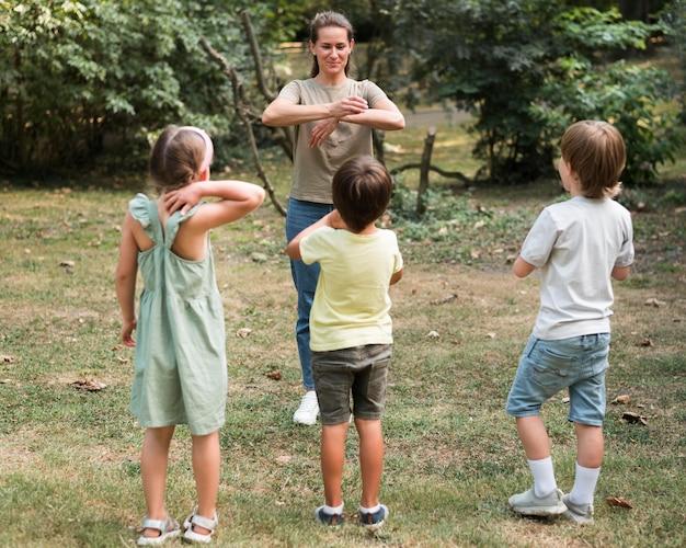 Полный снимок детей и учителей, играющих на открытом воздухе Бесплатные Фотографии