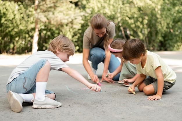 Bambini del colpo pieno che disegnano sulla terra Foto Gratuite