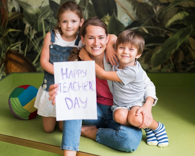 Полный снимок дети обнимают счастливого учителя Бесплатные Фотографии