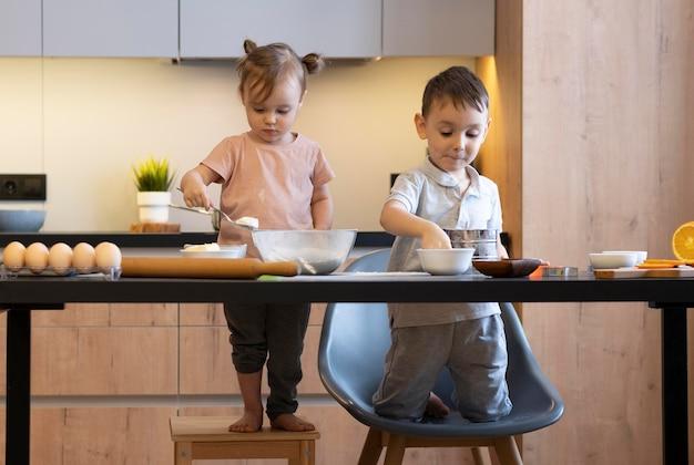 Bambini del colpo pieno che preparano il pasto insieme Foto Gratuite