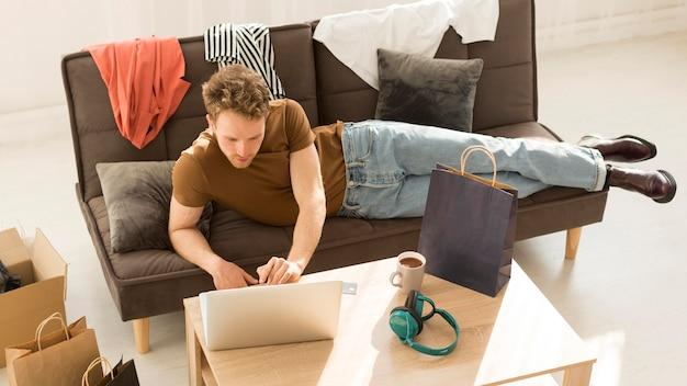 Uomo della foto a figura intera che esamina computer portatile Foto Gratuite
