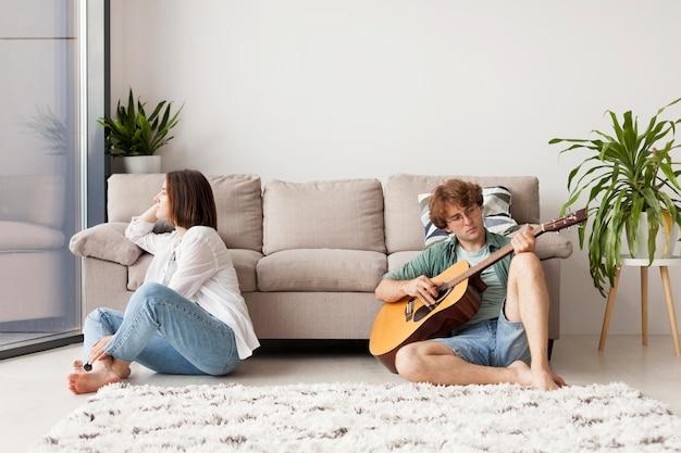 室内でギターを弾くフルショット男 無料写真