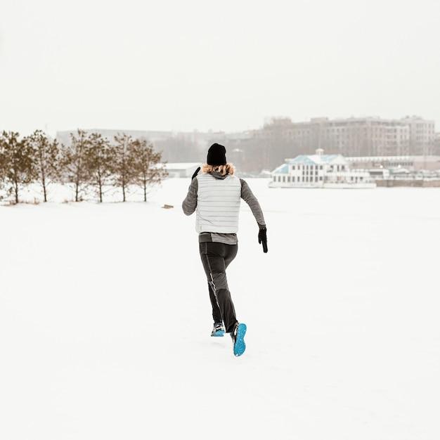 Полный выстрел человек работает в снегу Бесплатные Фотографии