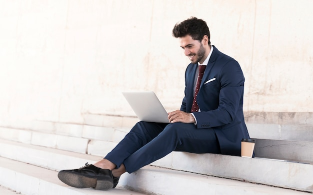 Full shot man in suit working on stairs Free Photo