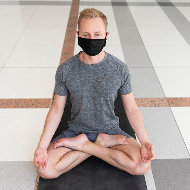 Полный снимок человека с маской для лица, делающего позу сукхасана в помещении Бесплатные Фотографии