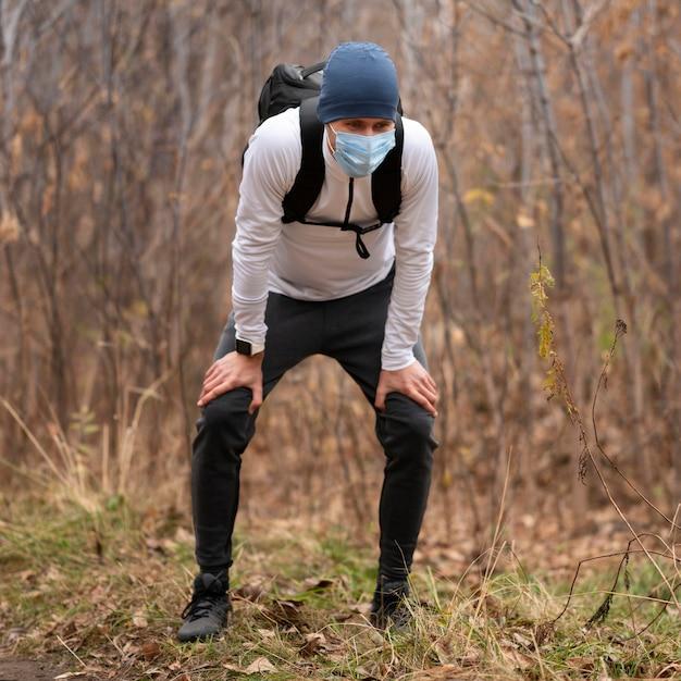 Полный снимок человека с маской для лица в лесу Бесплатные Фотографии
