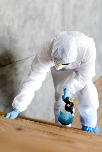 Full shot man with suit disinfecting stairs Free Photo
