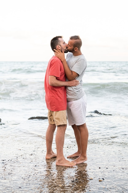 Full shot men kissing on shore Free Photo