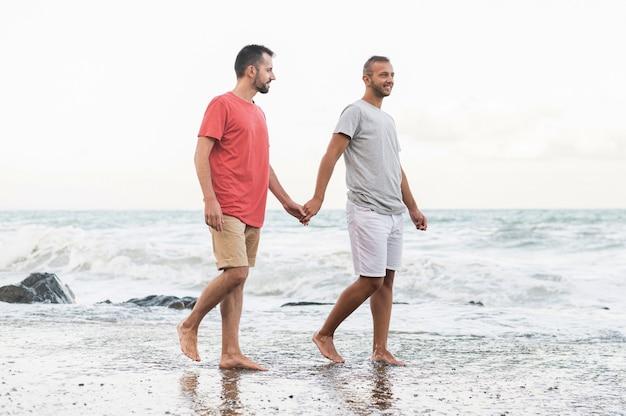 ビーチを歩くフルショットの男性 無料写真