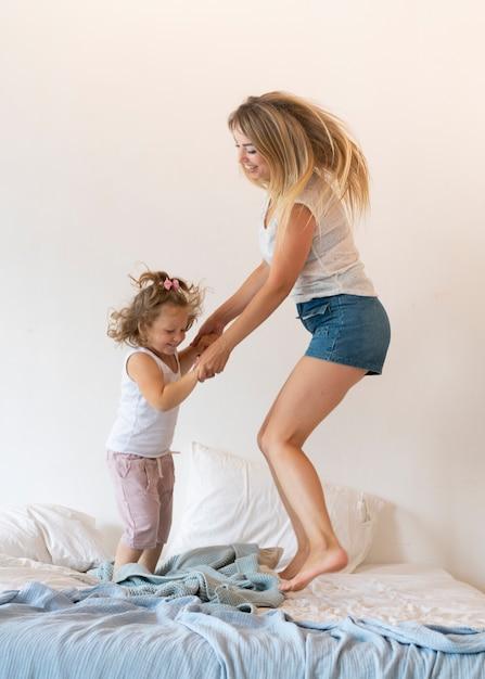 フルショットの母と娘がベッドの中でジャンプ 無料写真