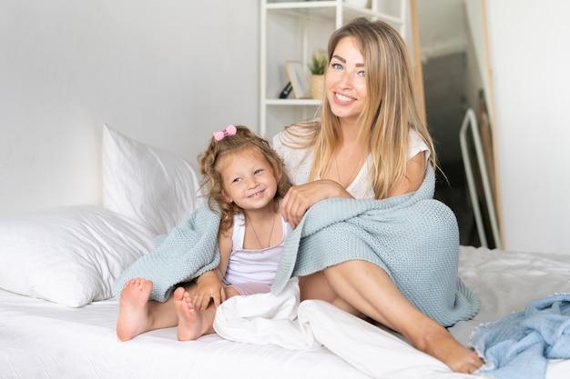 娘と一緒にベッドに座っているフルショットの母 無料写真