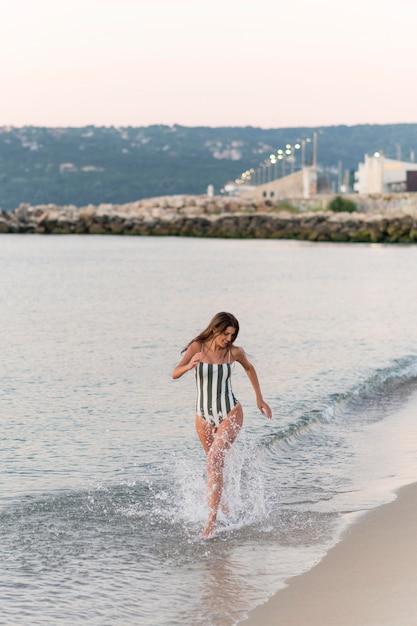 ビーチで美しい少女のフルショット 無料写真
