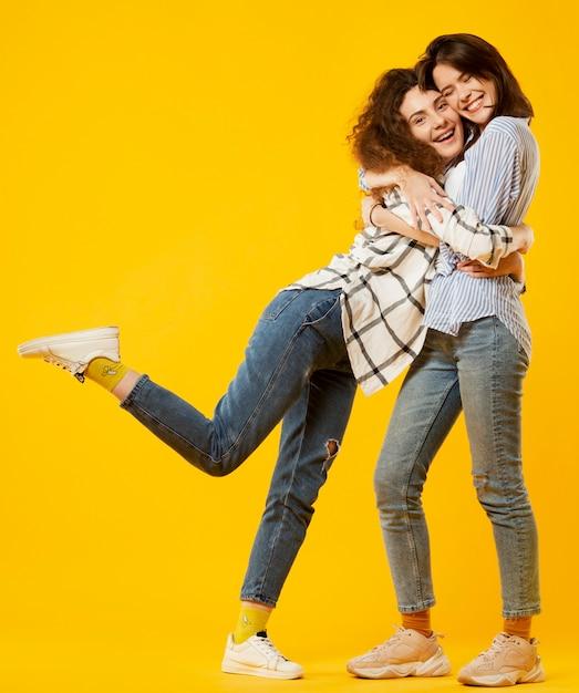 포옹하는 행복 한 친구의 전체 샷 프리미엄 사진