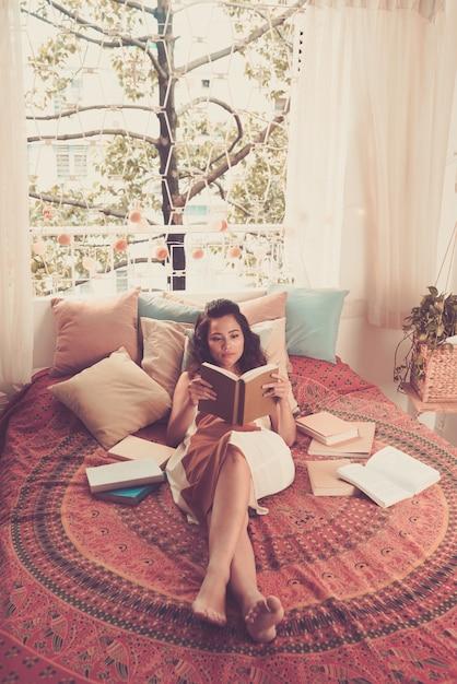Полный выстрел леди, читающей книгу, лежащую в ее кровати Бесплатные Фотографии