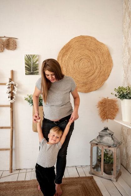 Full shot pregnant woman playing with toddler Free Photo