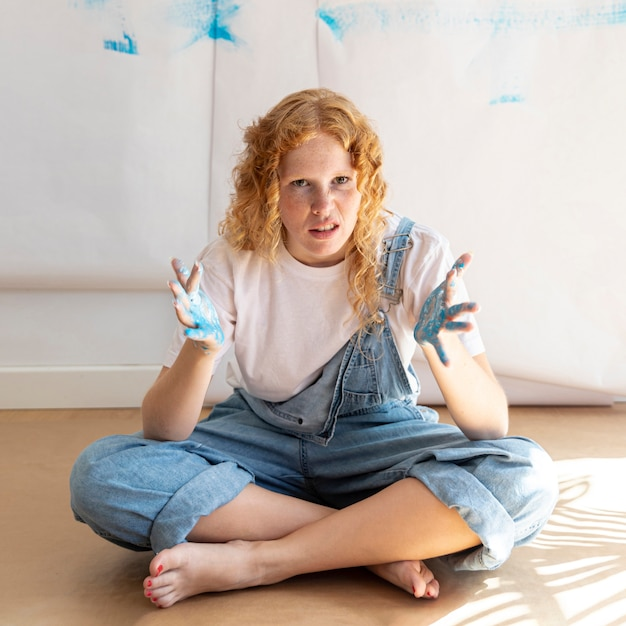Полный выстрел сидит женщина с нарисованными ладонями Бесплатные Фотографии