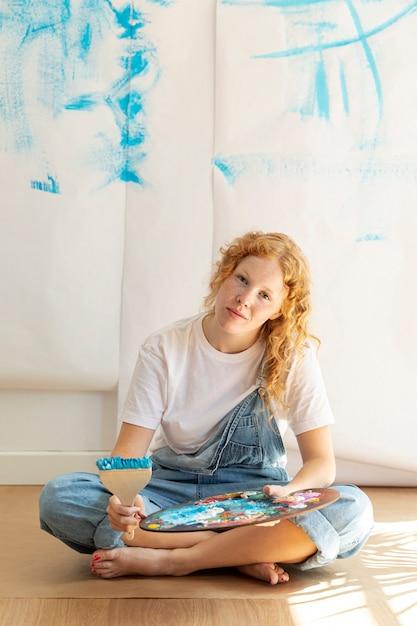 Полный выстрел сидит женщина с элементами живописи Бесплатные Фотографии