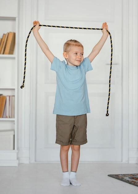 縄跳びを持っているフルショットの笑顔の少年 無料写真