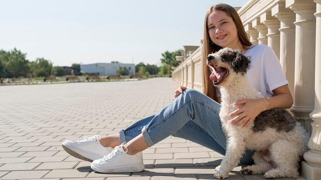 Ragazza piena di smiley del colpo che tiene cane sveglio Foto Gratuite