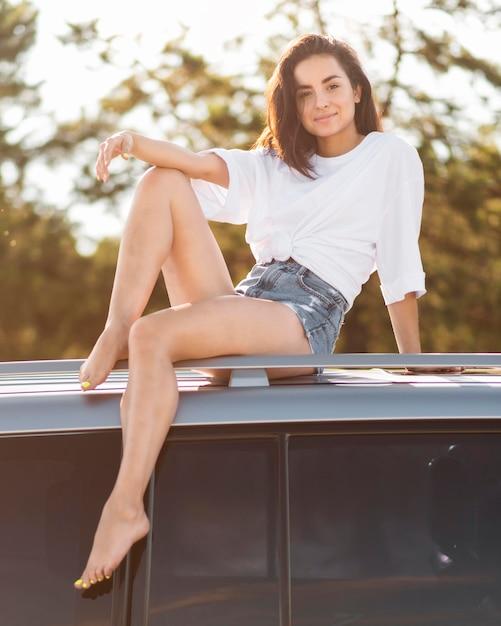 Donna piena di smiley del colpo che posa sull'automobile Foto Gratuite