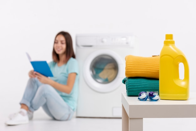 Full shot smiley woman reading and doing laundry Free Photo