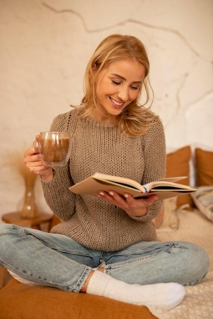 Полный выстрел смайлик женщина, читающая Premium Фотографии