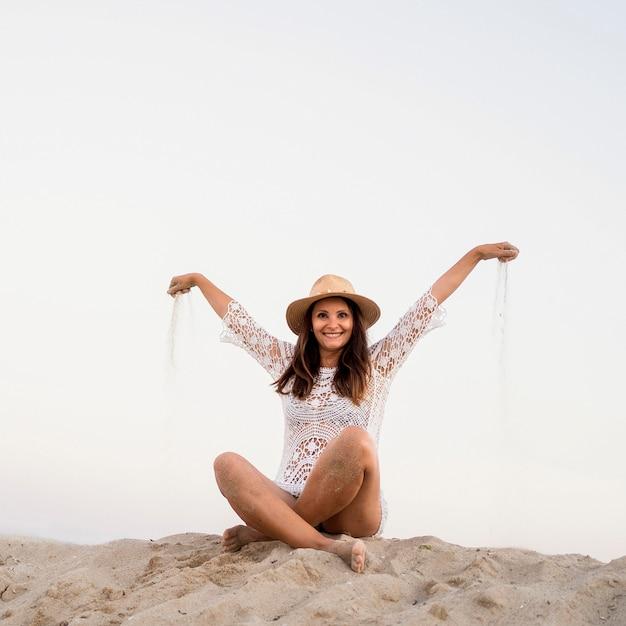Полный снимок смайлик женщина, сидящая на песке Бесплатные Фотографии