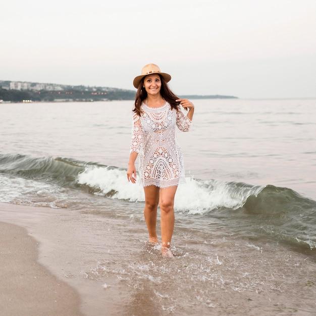 ビーチの上を歩くフルショットスマイリー女性 無料写真