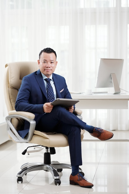 Full shot of successful asian business executive sitting cross-legged on his luxury boss chair in light spacious office Free Photo
