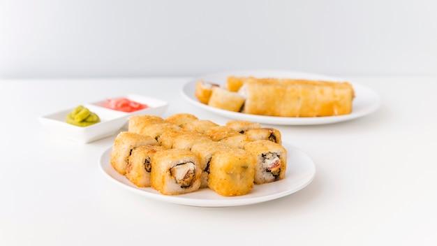 Full shot of sushi rolls on plates Free Photo