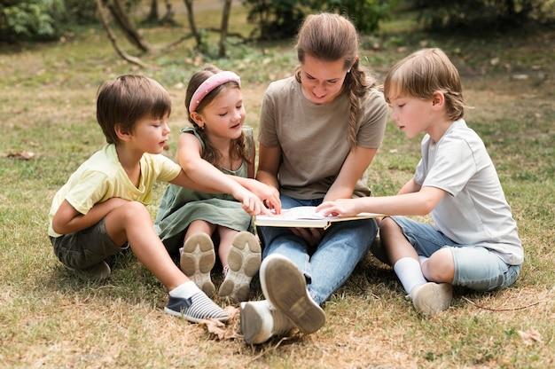 Insegnante del colpo pieno e bambini che tengono libro Foto Gratuite