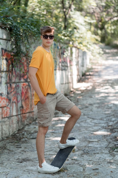 Ragazzo adolescente full shot con skateboard Foto Gratuite