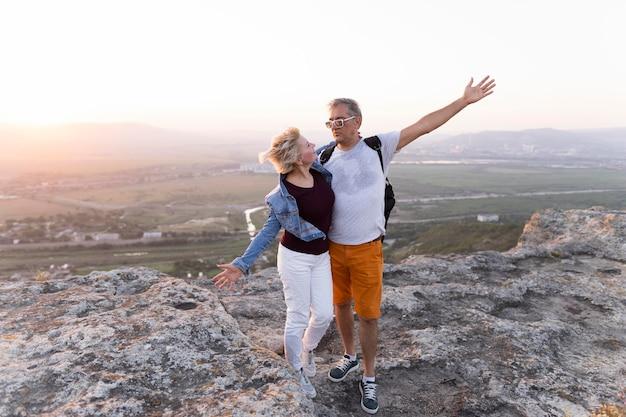 Полный снимок путешествия пара, стоящая на скале Бесплатные Фотографии