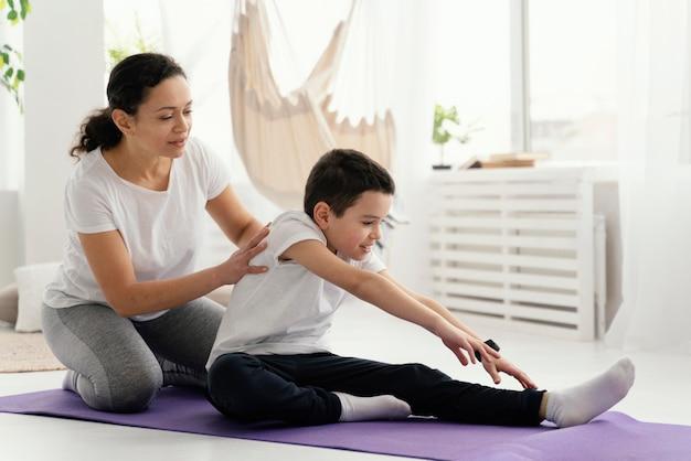 Женщина и мальчик в полный рост на коврике для йоги Бесплатные Фотографии