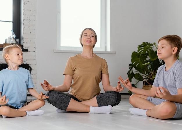 フルショットの女性と子供たちの瞑想 無料写真
